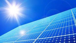 solar panels under blue sky and sun flare